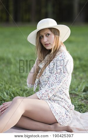 A beautiful girl with long blond hair and green eyes in a light hat in a short white dress and bare feet sits on a green grass in a flirtatious pose straightens her hair with her hand.