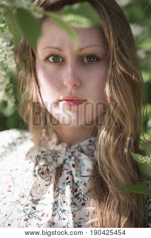 The face of a beautiful girl with long slightly wavy blond hair large bright green eyes and long black resils the girl is dressed in a white dress with a bow on her neck with a floral pattern against the background of green leaves of a tree.