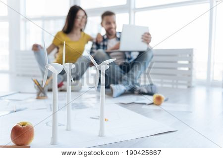 Alternative power resource. Selective focus of a windmill models standing on the floor with nice professional engineers working in the background