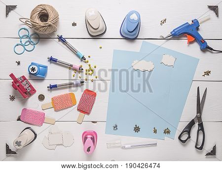 top view of wooden table with tools for scrapbooking and blank pages