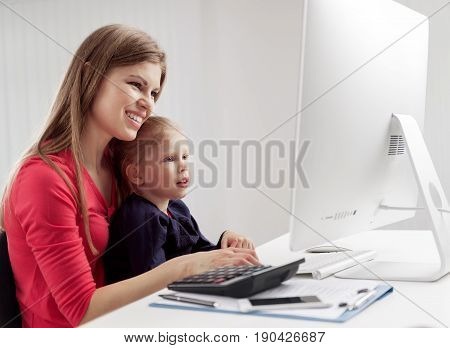 Young multitasking woman working in the office with her little child. Concept of business, family and lifestyle.