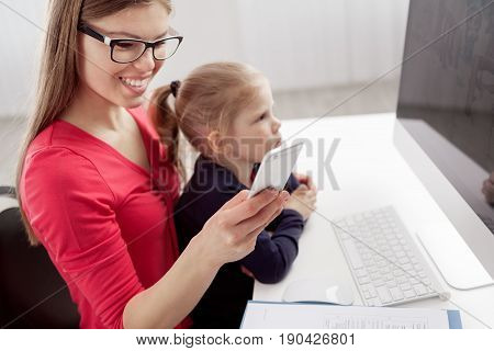 Happy smiling female texting message via smartphone while her small daughter studying pc. Concept of family occupation and lifestyle.