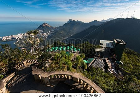 Rio de Janeiro, Brazil - May 24, 2017: View of Tijuca forest mountains from the Corcovado Mountain, with green umbrellas below, and a staircase to Christ the Redeemer statue.