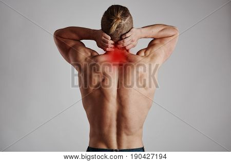 Neck pain. Athletic man massaging his inflamed spine.