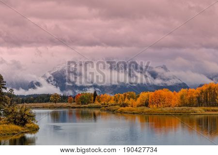 a scenic sunrise reflection of the Tetons in fall