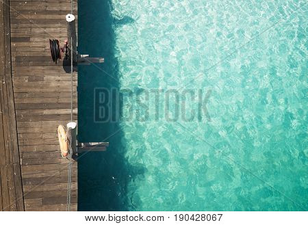 Wooden jetty with crystal clear and turquoise sea water of the tropical sea . Aerial top view .Rawa island Malaysia .