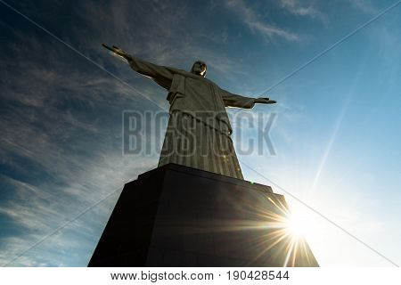 Rio de Janeiro, Brazil - May 24, 2017: Sun rays behind the Christ the Redeemer statue by sunset.