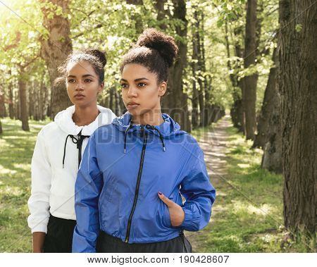 Two women wearing sport clothes in park, looking away