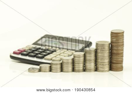pile of coins and calculator isolated on white background