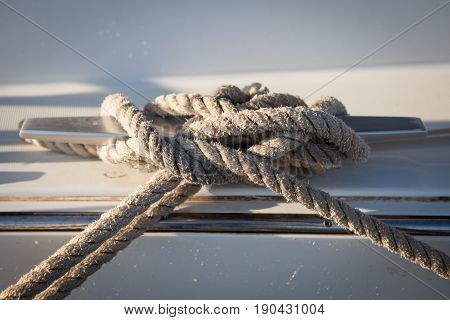 White mooring rope tied around steel anchor on a sailing boat or ship