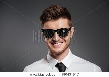 Close up portrait of a smiling stylish man in sunglasses and shirt looking at camera isolated over grey background