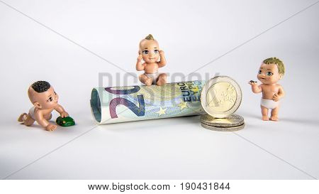 Small baby toys and euro money with white background children figures with euro bank notes and coins