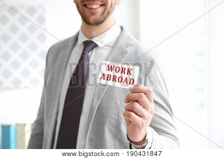 Young man holding business card with text WORK ABROAD on blurred background. Recruitment concept