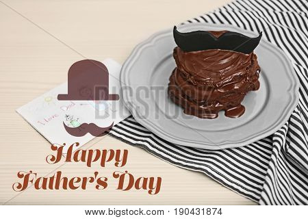 Plate with delicious chocolate pancakes, greeting card and text HAPPY FATHER'S DAY on wooden background