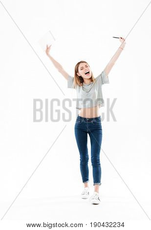 Full length portrait of a happy cheerful girl holding notepad and celebrating success with hands raised isolated over white background