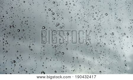 Closeup of raindrops on glass with rain clouds in the background