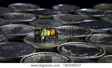 Silver chessboard silver coins with black background homeless sitting on the bank