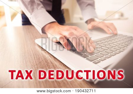 Tax deductions concept. Man working with laptop at table in office