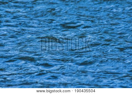 Perfect calm blue water ripples on a windless day