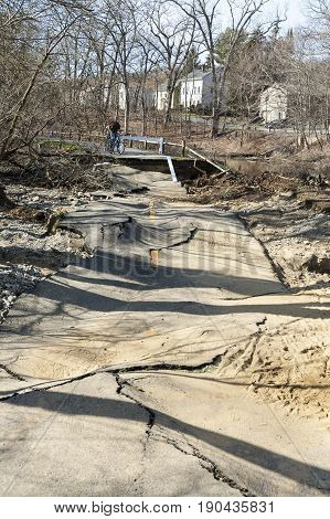 Lincoln Rhode Island USA - April 22 2007: Unidentified cyclists contemplate collapsed pavement on Blackstone River Bikeway from severe storm
