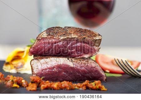 closeup of a cut steak with red wine