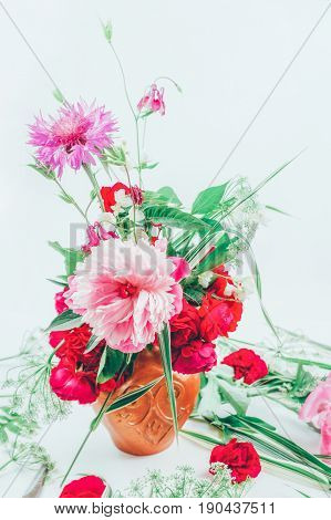 floral design. beautiful bouquet of pink flowers peons cornflowers and red roses tinted photo