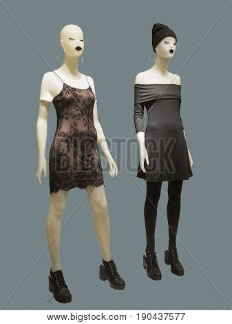Two full-length female mannequins wear fashion clothing. Isolated on gray background. No brand names or copyright objects.