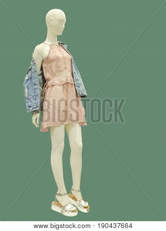 Full-length female mannequin dressed in blue jeans jacket and pink dress. Isolated on green background. No brand names or copyright objects.