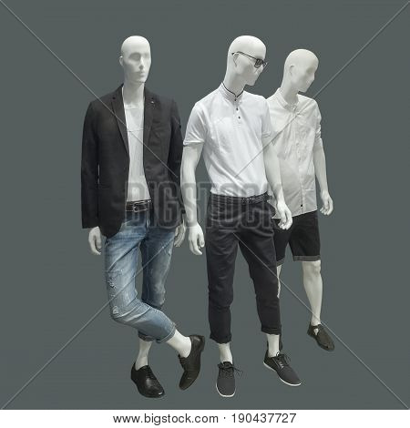 Three man mannequins dressed in casual clothes over gray background. No brand names or copyright objects.