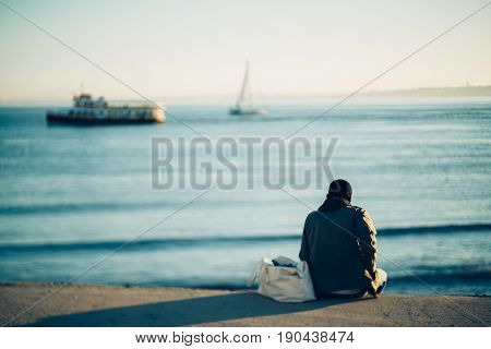 True tilt-shift shooting of lonely afro american guy with short haircut sitting on pier alone and enjoying view of beautiful sunset and two vessels sailing across the river with teal calm water
