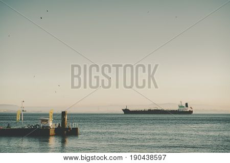 Huge barge or cargo ship slowly passing by in distance low hills on misty horizon and part of dock in foreground with flags and white booth sunny summer day with teal water and clear sky with birds