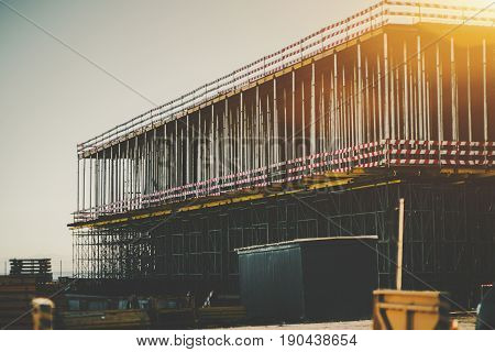 Two-storey massive building under construction near coastline of Lisbon with many regular vertical metal beams scaffoldings and construction stuff around on sunny summer day with clear sky