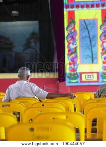 rear view of an old man in front of chinese opera stage