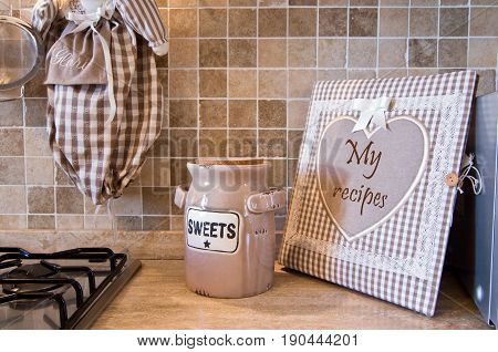 Fitted kitchen with warm and welcoming colors with grandma's cookbook and biscuit box