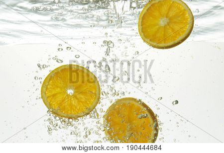 slices of oranges in water with bubbles