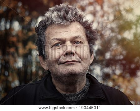 The man in the face with piercing eyes. Portrait of a man at the age on the background of autumn forest