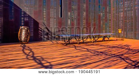 tiled roof terrace with a bench enclosed by rusty steel panel, Marseille