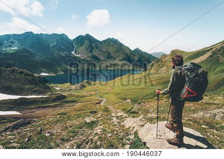 Traveler Man enjoying lake and mountains view Travel Lifestyle concept adventure summer vacations outdoor wayfarer with backpack