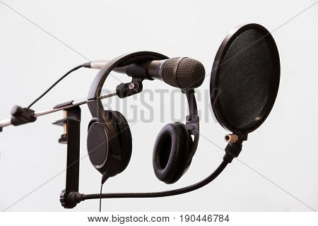 Cardioid condenser microphone, headphones and pop filter on a gray background. Home recording Studio.