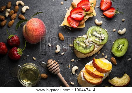 Fresh sweet fruit sandwiches. Strawberry peach and kiwi sandwiches with nuts and honey over black slate table. Top view. Healthy snack.
