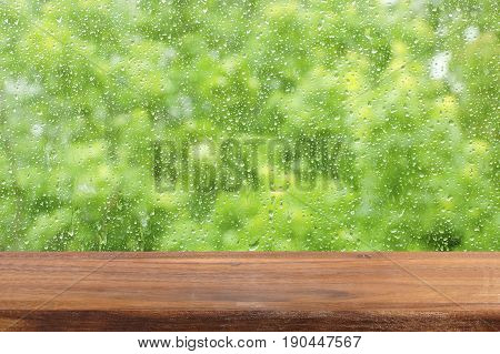 An empty wooden table by the window. Rain drops on the glass. Free place for creativity. Background.
