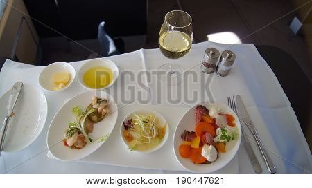 FRANKFURT, GERMANY - SEPTEMBER 28, 2014: First Class Dining onboard an Boeing 747 upper deck from Lufthansa, white wine, water and appetizer.