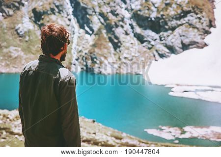 Man wander icy lake in mountains landscape Travel Lifestyle adventure concept summer vacations outdoor harmony with nature