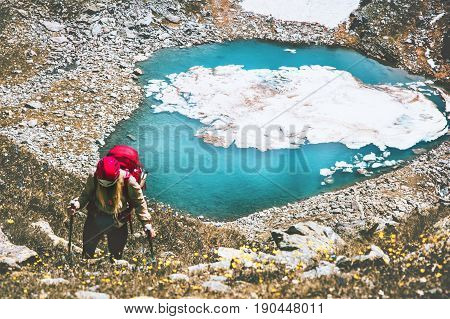 Hiker woman climbing at blue lake heart shaped mountains with backpack Travel Lifestyle adventure concept summer vacations outdoor active healthy life