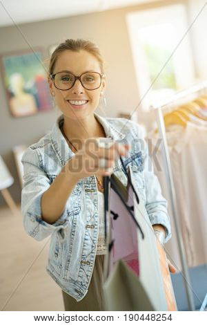 Cheerful salesperson handing shopping bag to customer