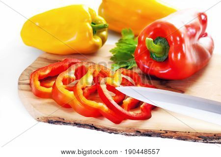 Wooden cutting board with red bell pepper and yellow bell pepper whole and sliced.