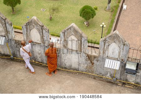May 11 2017. Aerial view of a Buddhist novice monk and his young attendant gazes a downtown view from the top of the historical Patuxai monument. Vientiane Laos. Travel and people editorial concept.