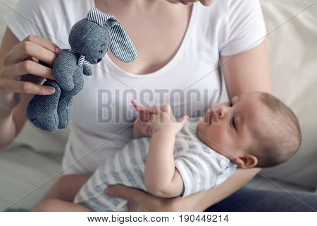 mother with her newborn son in hands sitting on a big white bed and shows a rabbit toy