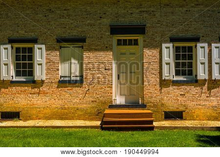 A doorway of a brick house in partial shadows