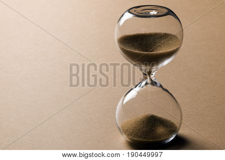 Sand clock with leaking sand on beige background time concept.